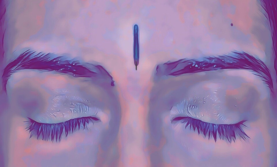 Person's face with acupuncture needle in acu point Yin Tang, between the eyebrows.